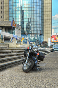 classic-motorcycle-parked-in-front-of-a-modern-glass-building