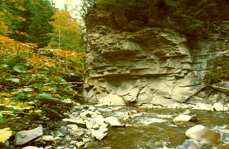 Mountain-river-with-a-stone-wall-and-a-small-bridge